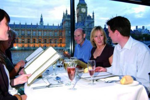 People Enjoying Dinner about a Bateaux London Boat